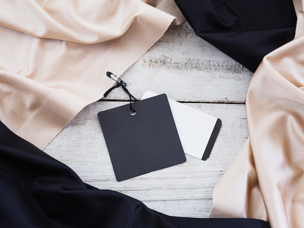 Cierre etiqueta de venta de papel negro colgando de tela de seda sobre fondo blanco de madera vintage.