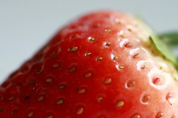 Cierre fresco de la fresa para arriba, macro en el fondo blanco
