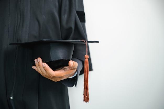 Cierre el gorro de graduación y el gorro de graduación tassle durante el inicio del título universitario