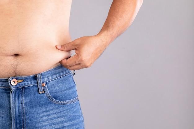 Cierre de hombre gordo pellizcando su barriga izquierda con. gente gorda y concepto saludable
