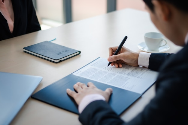 Cierre de hombre de negocios escribiendo o firmando contrato en papel en la oficina.