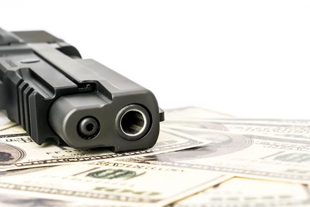 Cierre de la imagen de la pistola y el dólar.