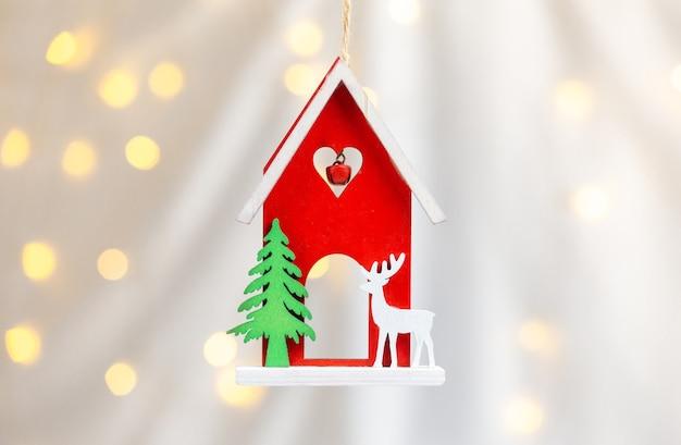 Cierre de juguete de navidad de madera. casa con ciervos.