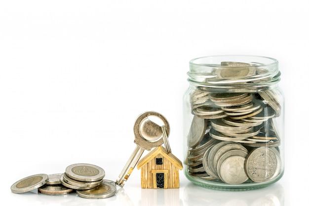 Cierre el lugar de la casa modelo en el apilamiento de monedas de dinero para una hipoteca y un préstamo hipotecario