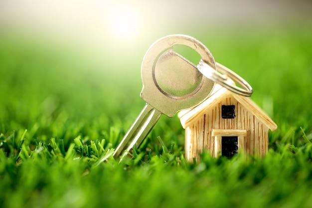 Cierre el lugar del modelo de la casa en la hierba verde para hipotecas y préstamos hipotecarios, refinanciamiento o una inversión inmobiliaria