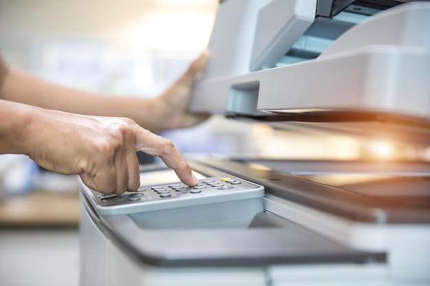 Cierre la mano del hombre de la oficina presione el botón en el panel de la fotocopiadora.