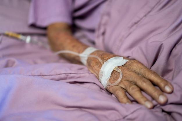 Cierre en la mano del paciente anciano con un tubo de solución salina normal, el paciente anciano recibe una solución salina normal a través de la jeringa hipodérmica (inyector).
