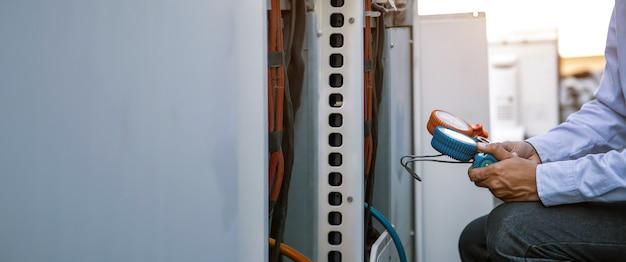 Cierre la mano del técnico que usa el manómetro del colector para llenar los acondicionadores de aire.