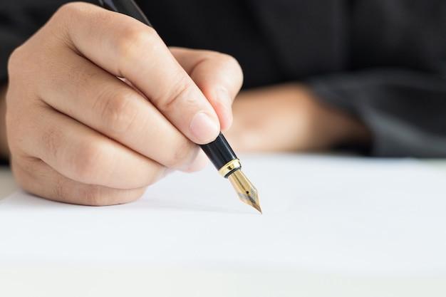 Cierre de la mano del tiro de la mujer de negocios que usa la pluma para escribir en el enfoque selectivo del libro blanco profundidad del campo baja
