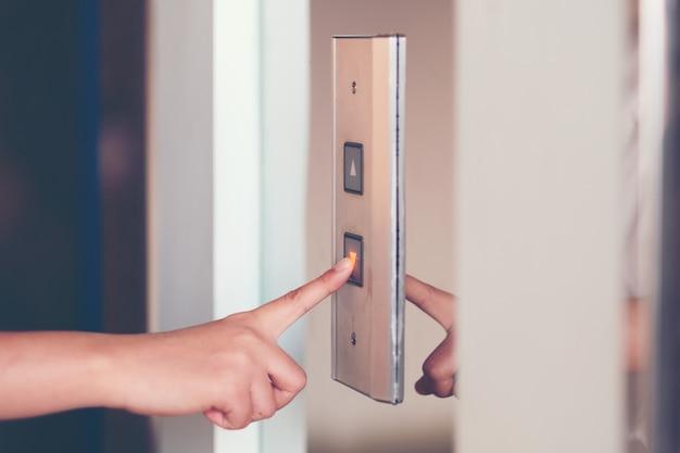 Cierre la mano de waman presione un botón arriba del ascensor dentro del edificio para el piso de nivel inferior.