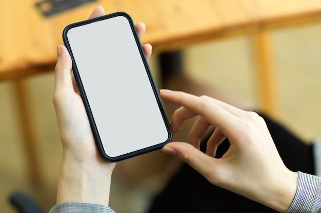 Cierre la maqueta de la pantalla en blanco del teléfono inteligente, pantalla blanca para montar el cartel de su marca sosteniendo por manos femeninas, teléfono móvil con fondo borroso