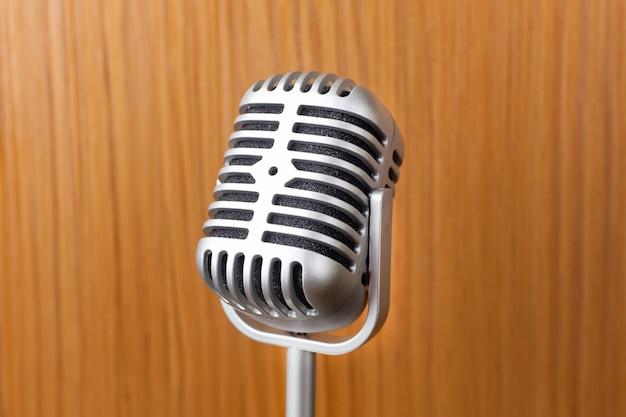 El cierre del micrófono del vintage encima de la imagen en el fondo de madera.