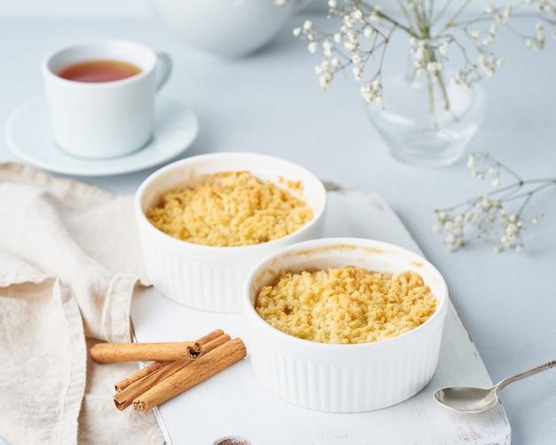 Cierre de migaja de manzana con streusel. vista lateral. desayuno de la mañana en una mesa de color gris claro.