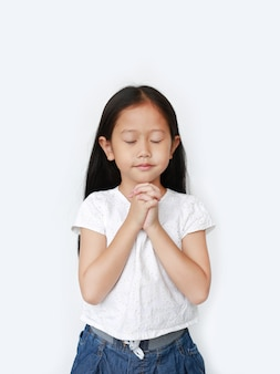 El cierre observa la pequeña muchacha asiática hermosa del niño que ruega aislado. espiritualidad y religión.