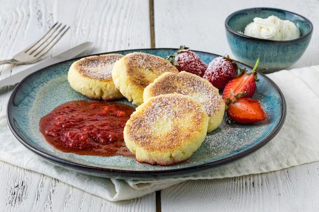 Cierre los panqueques de queso, syrniki, buñuelos de cuajada con fresas frescas en la mesa de platos