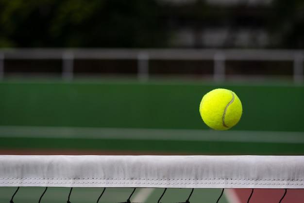 Cierre de pelota de tenis en el fondo de red con espacio de copia