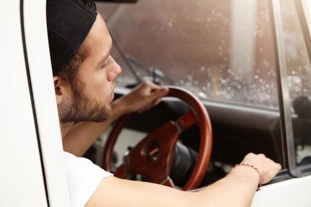 Cierre plano de atractivo hipster caucásico joven vistiendo camiseta y gorra de béisbol al revés, sentado dentro de su vehículo de safari blanco con la mano en el volante