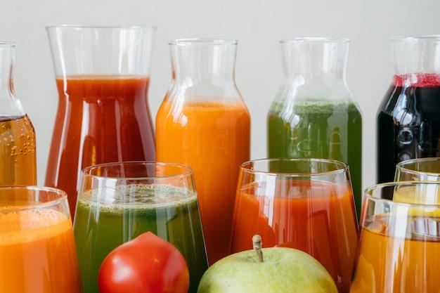 Cierre plano de botellas de vidrio llenas de jugo colorido hecho de diversas verduras y frutas.