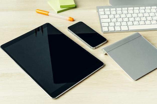 Cierre plano de dispositivos digitales en la mesa de oficina