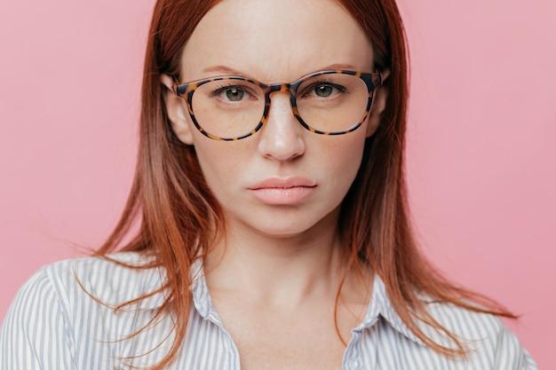 Cierre plano de encantadora modelo femenino lleva gafas ópticas grandes