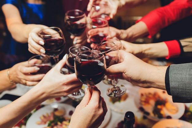 Cierre plano de grupo de personas tintinear vasos con vino o champán delante de fondo bokeh