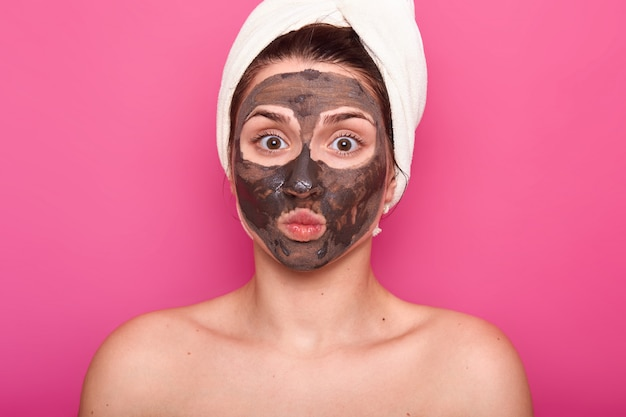 Cierre plano de hermosa mujer, tiene máscara de chocolate en la cara, mantiene los ojos bien abiertos y los labios redondeados, posa con el cuerpo desnudo, tiene una toalla blanca en la cabeza, descansa en el salón de spa, aislado en la pared de color rosa.