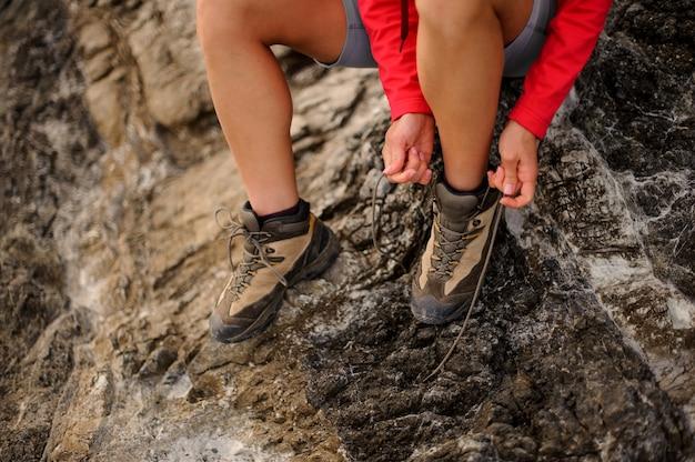 Cierre plano de mujer excursionista tiyng cordones de los zapatos