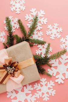 Cierre plano de pequeño regalo envuelto con cinta sobre fondo rosa