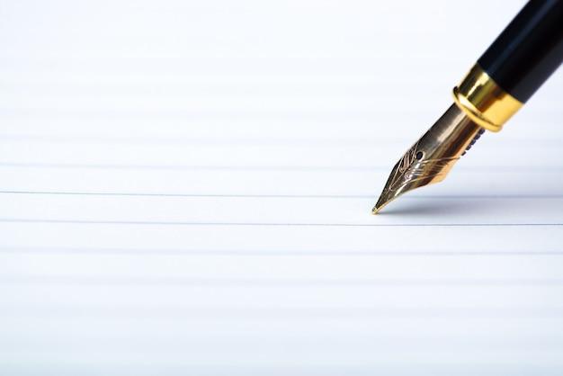 Cierre de pluma estilográfica o tinta con papel de cuaderno en mesa de trabajo de madera