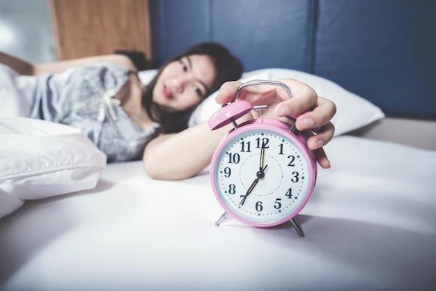 Cierre de reloj de enfoque selecto con hermosa mujer en dormitorio
