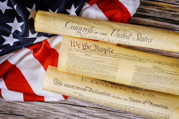 Cierre de una réplica del documento de los estados unidos de la constitución estadounidense nosotros, la gente con la bandera de estados unidos.