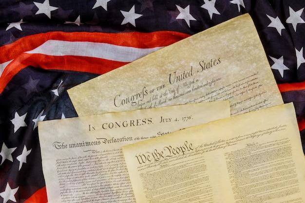 Cierre de una réplica del documento de los estados unidos de la constitución estadounidense nosotros, las personas con la bandera de estados unidos