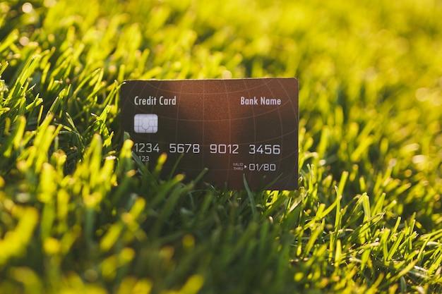 Cierre la tarjeta negra del banco de crédito en la hierba de golf fresca verde primavera vibrante, césped de sol. textura de la naturaleza, fondo verde para papel tapiz. enfoque suave. diseño de concepto de campo o finanzas. copie el espacio.