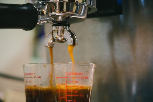 Cierre de tiro de café crema una máquina de café espresso vertido en el vaso de la taza de café tiro simple y doble por barista en la cafetería cafetería.