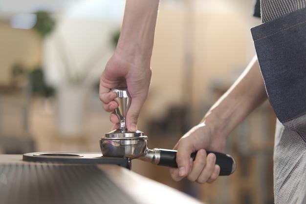 Cierre de la vista del barista que aplasta el grano de café molido en el café tamp en la estera tamp.