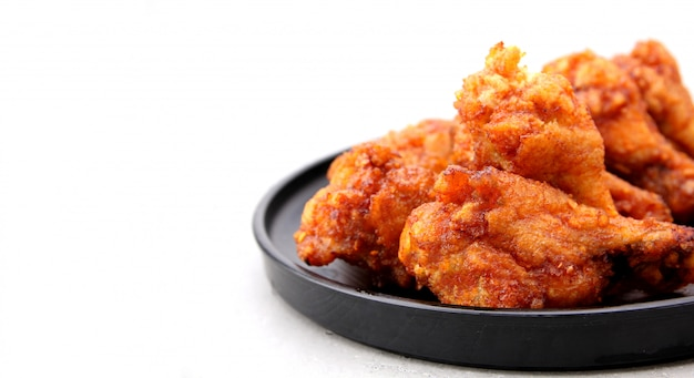 Ciérrese hasta las alitas de pollo fritas coreanas aisladas en un fondo blanco en estudio