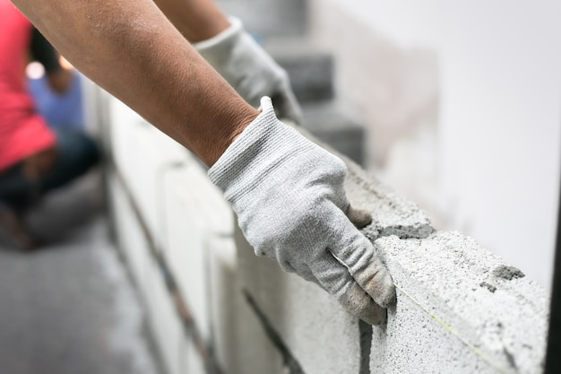 Ciérrese para arriba del albañil industrial que instala ladrillos en el emplazamiento de la obra, construyendo las paredes.