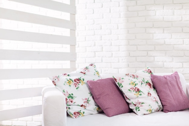 Ciérrese para arriba de almohadas coloridas en el sofá en sala de estar moderna