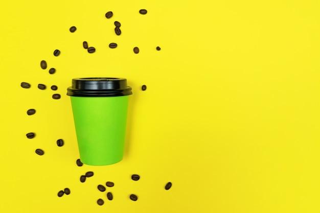 Ciérrese para arriba del café para ir taza en fondo amarillo brillante. concepto de eco. lugar para el texto.