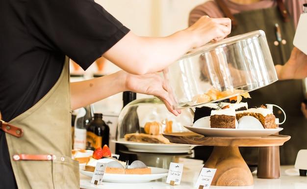 Ciérrese para arriba del camarero joven que sostiene la tapa de cristal sobre la torta en soporte de la torta en el contador en cafetería