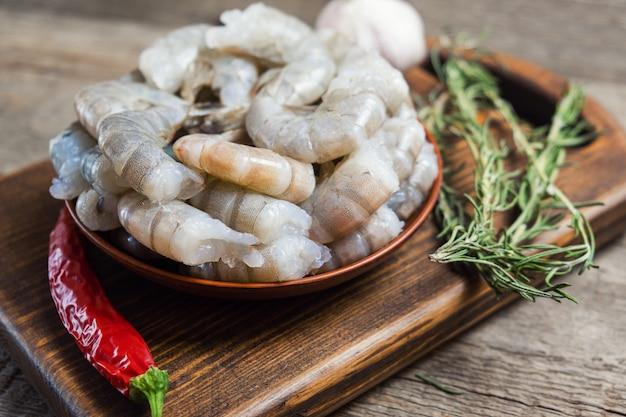 Ciérrese para arriba de camarones crudos en fondo de madera.