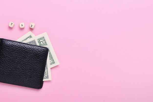 Ciérrese para arriba de la cartera negra en un fondo rosado con el impuesto de la palabra de letras de madera. vista superior, minimalismo