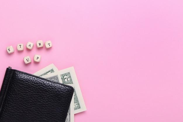 Ciérrese para arriba de la cartera negra en un fondo rosado con las palabras puesta en marcha de letras de madera. vista superior, minimalismo