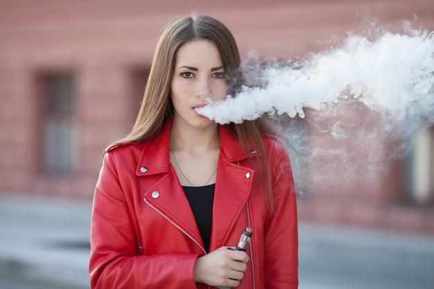 Ciérrese para arriba de la chica joven del vaping que sostiene el dispositivo moderno del e-cig en labios. fumando nicotina del traje. mujer joven del fumador con el artilugio electrónico del cigarrillo.