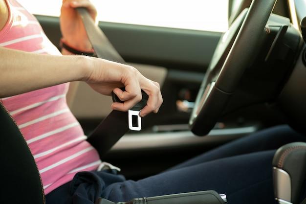 Ciérrese para arriba del cinturón de seguridad de la cerradura de la mano de la mujer mientras que se sienta dentro de un coche para la seguridad antes de conducir en el camino. conductor femenino que conduce con seguridad y toma con seguridad a jordan.
