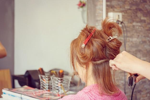 Ciérrese para arriba del corte de pelo de las mujeres en el fondo borroso salón de pelo, foco selectivo.