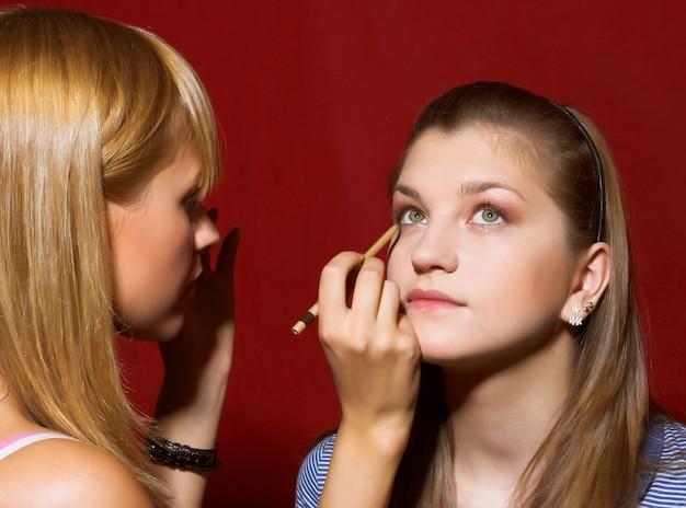 Ciérrese para arriba del cosmetólogo que crea el maquillaje para mujeres jovenes en el salón de belleza.