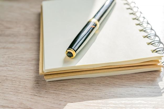 Ciérrese para arriba del cuaderno y de la pluma vacíos de kraft en la tabla de madera