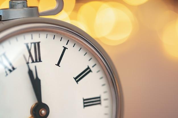 Ciérrese para arriba del despertador retro en fondo borroso de la navidad con el bokeh