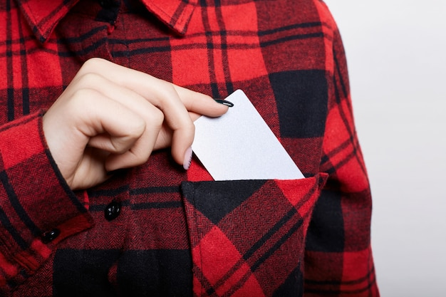 Ciérrese para arriba de la empresaria que sostiene la tarjeta de visita en blanco. joven mujer sacando la tarjeta de negocios del bolsillo de su camisa roja a cuadros